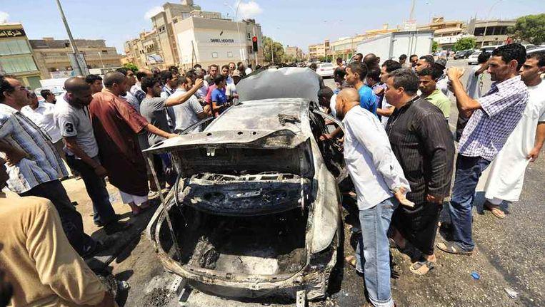Omstanders bekijken het wrak van een auto na ontploffing van een autobom in Benghazi, dinsdag. Beeld reuters