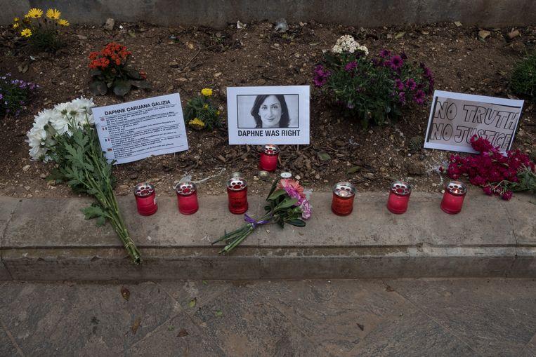 Bloemen en waxinelichtjes bij een monument voor Caruana Galizia in Valletta. Beeld Joanna Demarco
