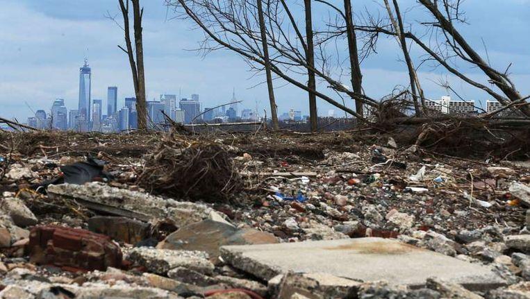 De schade die de storm Sandy aanrichtte met op de achtergrond New York. Extreem weer komt steeds vaker voor en is 'een gevaar voor de veiligheid' volgens de Amerikaanse veiligheidsdienst. Beeld afp