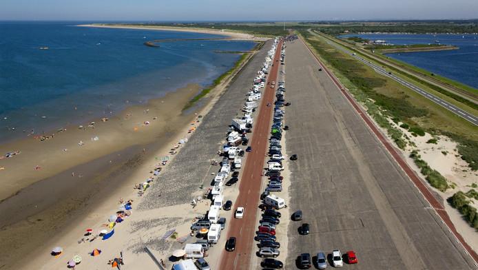 Een luchtfoto van badgasten, campers en auto's op de Brouwersdam.