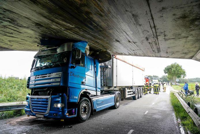 De vrachtwagen kwam klem te zitten onder een viaduct aan de Kurenpolderweg in Hank.