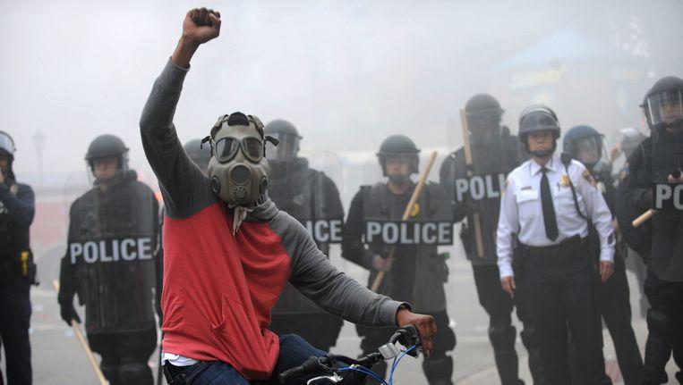 Een demonstrant bij een linie van de oproerpolitie in de Amerikaanse stad Baltimore, na de begrafenis van Freddie Gray die dodelijk gewond raakte bij zijn arrestatie. Beeld AP