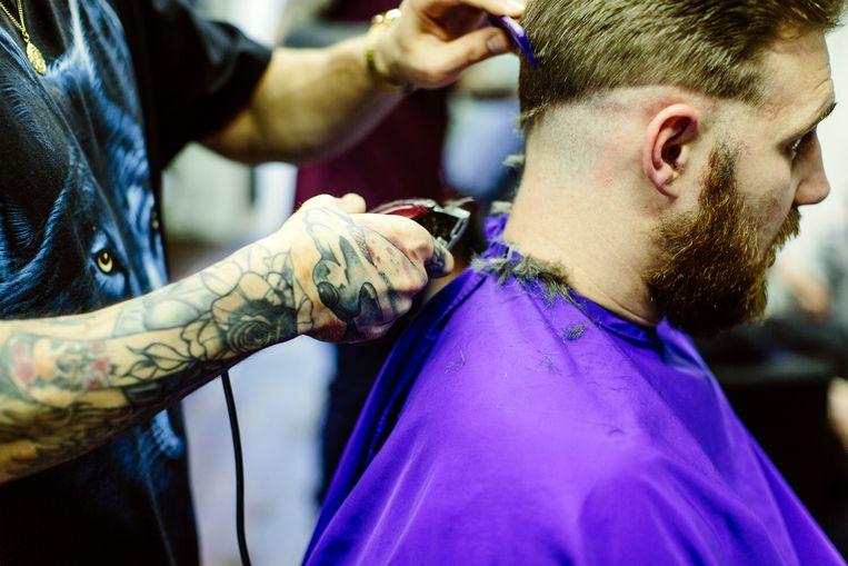 Een kapper werkt de haarlijn bij.