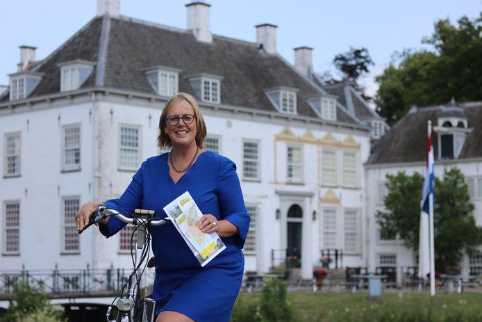 Ineke Hissink, voorzitter van de organisatie achter de Open Monumentendag, op de fiets voor het monument dat dit jaar haar favoriet is: Huis 't Veld.