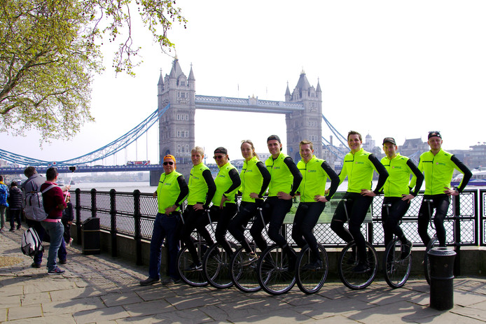 Het Juliana Bicycle Team poseert nabij de Tower Bridge in Londen. Het team gaat per eenwieler in tien dagen van Londen naar Millingen aan de Rijn.