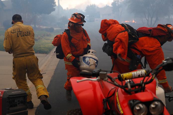 Een brandweerman haalt een gasfles weg uit een brandend huis in Paradise.