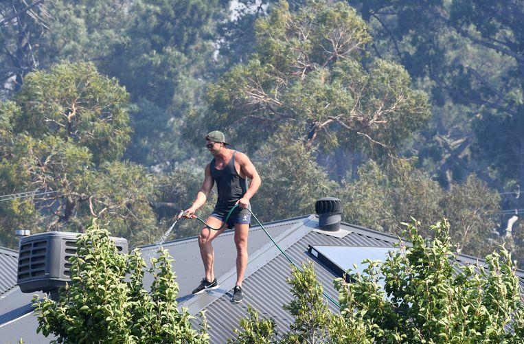 Een man is het dak van zijn huis aan het afkoelen in Melbourne. Intussen is het te laat om het gebied nog te ontvluchten, want al heel wat bossen in het westen van Victoria staan intussen in brand.