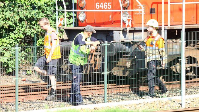 Medewerkers zijn bezig de trein weer op de rails te krijgen.