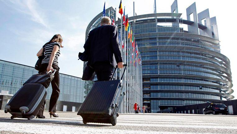 Leden van het Europees Parlement lopen met hun koffers op weg naar het parlement in Straatsburg Beeld reuters