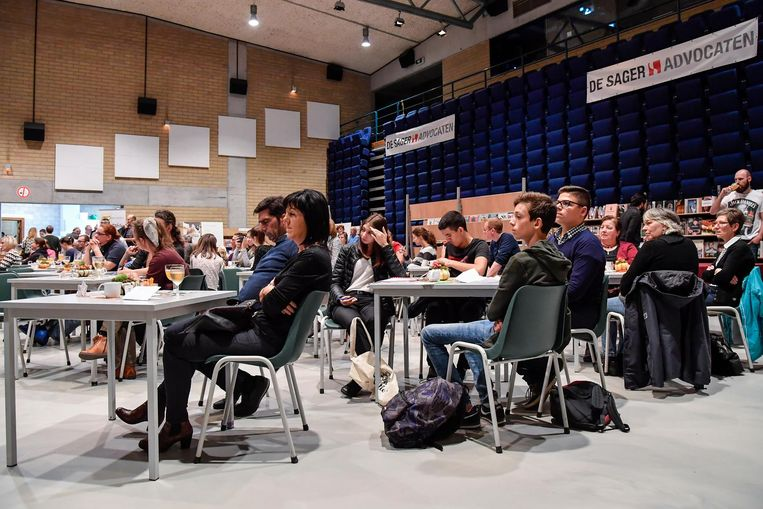 Bezoekers nemen plaats in de zaal en luisteren naar wat de auteurs te zeggen hebben.