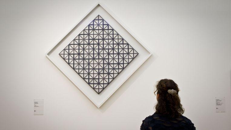 Een vrouw kijkt naar een van de werken van schilder Piet Mondriaan © ANP Beeld