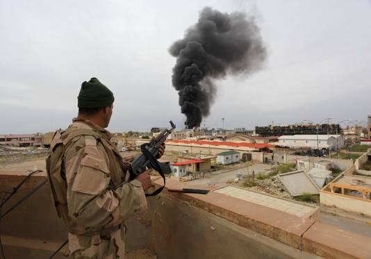 Een veiligheidsagent kijkt vanaf de basis uit over Tikrit