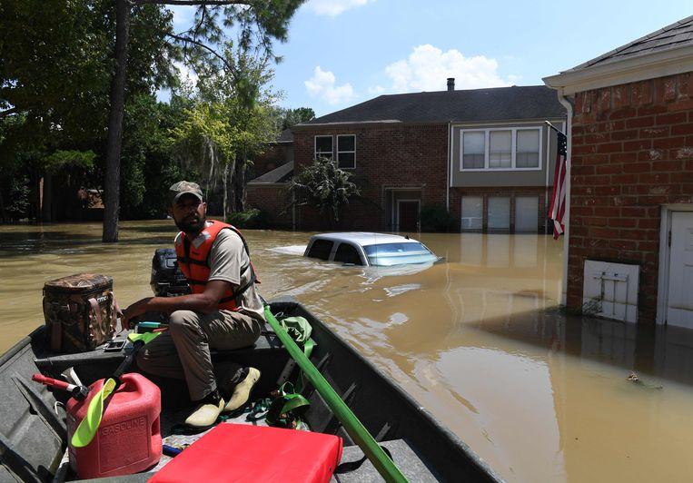 Een vrijwilliger zoekt bewoners in het rampgebied die nog geevacueerd moeten worden. Beeld AFP