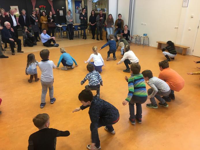 Eva Holtzer verzorgt met Groep 5 van basisschool de Kleine Akkers een dansdemonstratie. Guus van de Put, wethouder in Goirle, schroeft met Maartje van den Boom het Cultuureducatie-bordje op de gevel van bsisschool de Kleine Akkers.