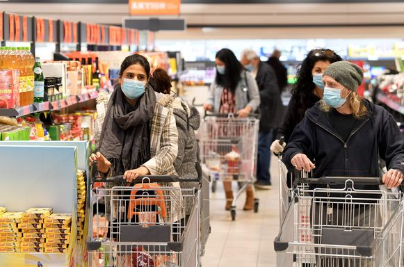 Klanten met mondmaskers in een supermarkt in Wenen vandaag. Vanaf nu is het verplicht in Oostenrijk om in supermarkten een masker te dragen.