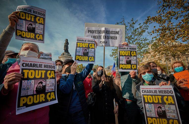 Betogers houden een kopie van het satirische blad Charlie Hebdo omhoog tijdens tijdens de demonstratie voor de vrijheid van meningsuiting, afgelopen zondag in Parijs. Beeld Getty Images