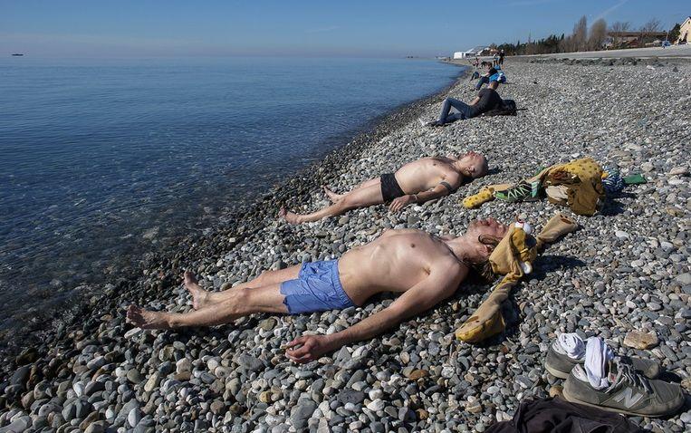 Russische mannen werken aan hun kleurtje langs de Zwarte Zee, nabij het olympisch stadion Fisjt Beeld epa