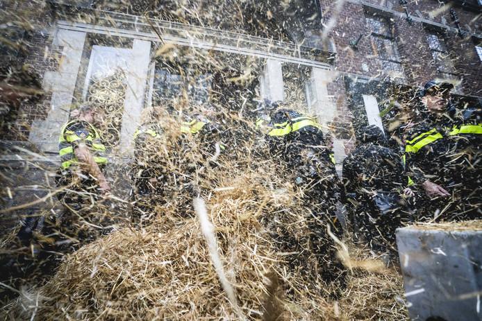 Politieagenten werden maandag in Groningen met stro bekogeld tijdens het boerenprotest voor het provinciehuis.