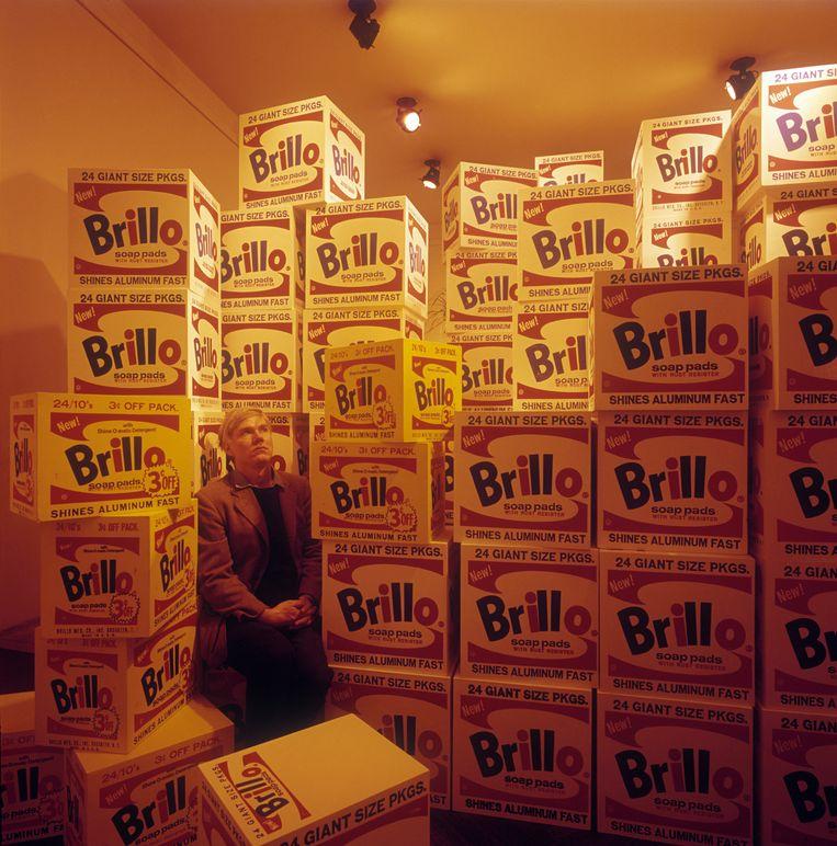 Kunstenaar Andy Warhol poseert tussen zijn Brillo-dozen, in 1964. Beeld Getty Images