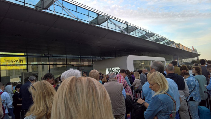 Honderden mensen staan buiten te wachten voor het hoofdgebouw van de luchthaven.