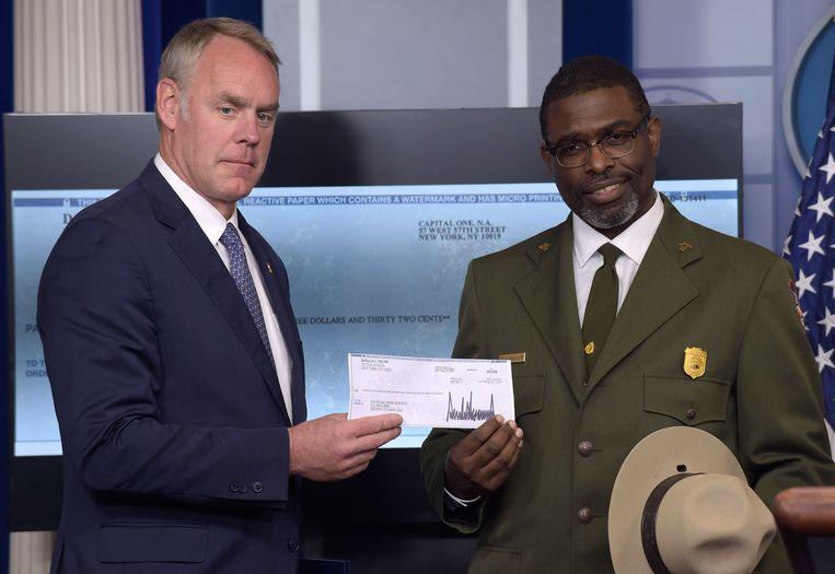 Secretaris Ryan Zinke geeft de cheque aan Tyrone Brandyburg van de National Parks Service.