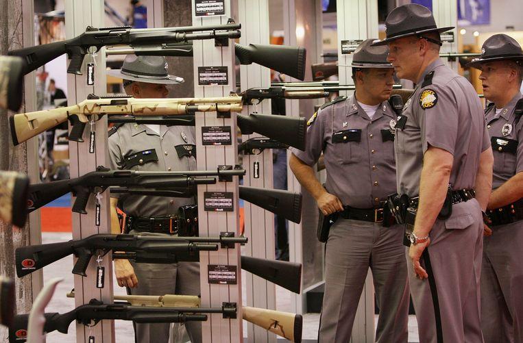 Agenten in Kentucky kijken naar wapens tijdens de jaarvergadering van de NRA in Louisville.  Beeld AFP