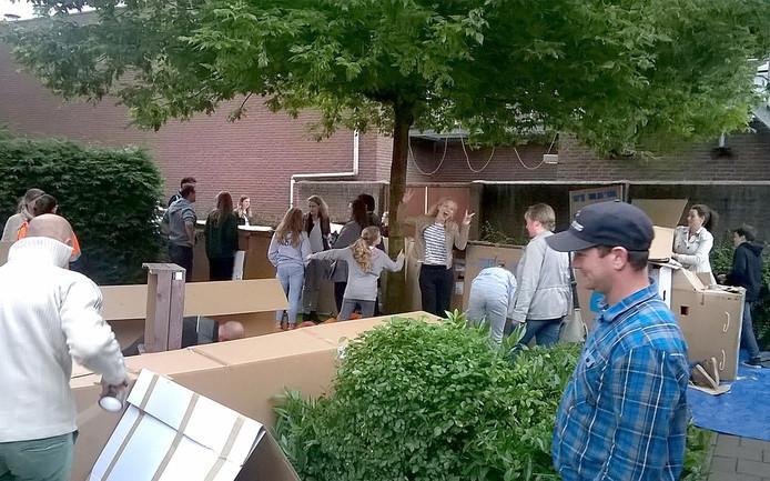 29 jongeren tussen de 11 en 17 jaar in een hut van fietsdozen in de tuin van de Hervormde Kerk in Zevenbergen