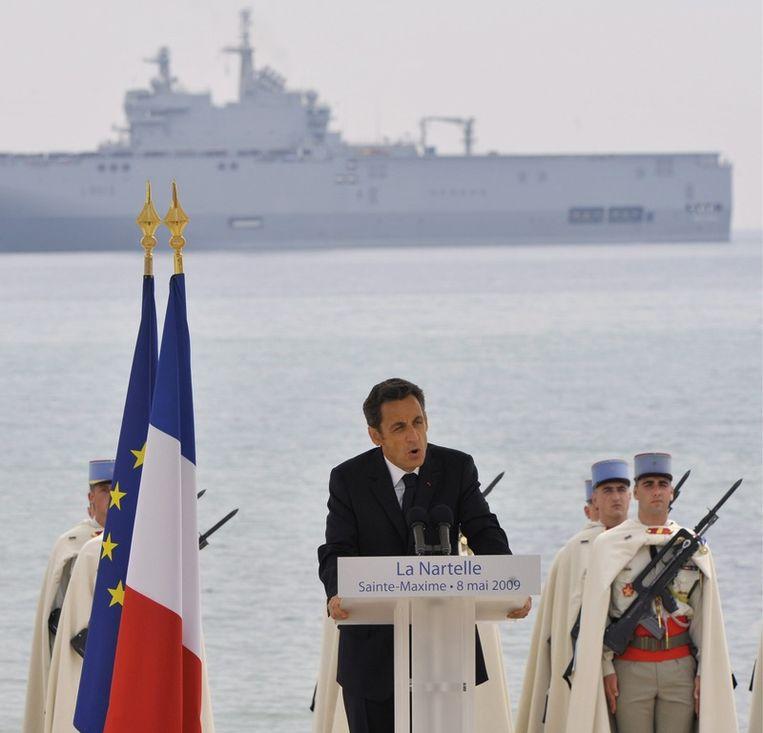 De Franse president Sarkozy, tijdens een herdenking van de overwinning op Nazi-Duitsland. Op de achtergrond een Mistral-schip. © afp Beeld