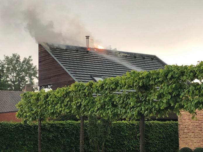 De brandweer blust de brand, die ontstaat door blikseminslag.
