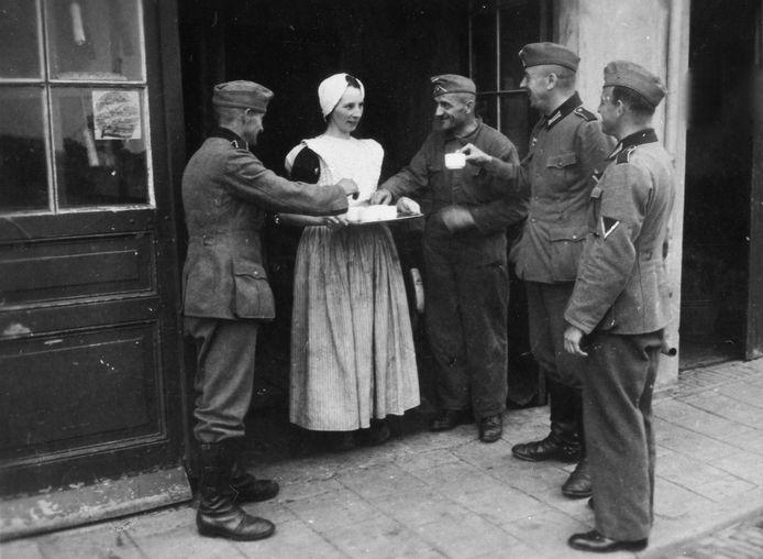 Driewegen (Zuid-Beveland), 16 mei 1940: Duitse militairen bij de wagenmakerij van Jozias Lansen. Maria Lansen haalde 'ein Kann frisches Wasser', een militair pakte uit zijn ransel een flacon limonadesiroop en verdeelde limonade. fotograaf onbekend, ZB, Beeldbank Zeeland