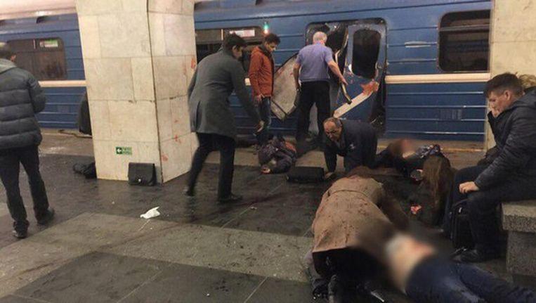 Passagiers helpen gewonden bij een metrostation in Sint-Petersburg. Beeld Twitter