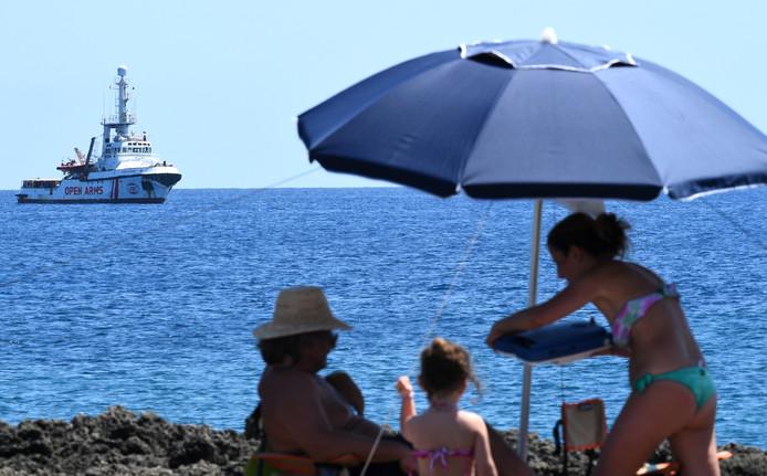 Le navire dans l'attente d'une réponse tandis que les vacanciers profitent de la plage