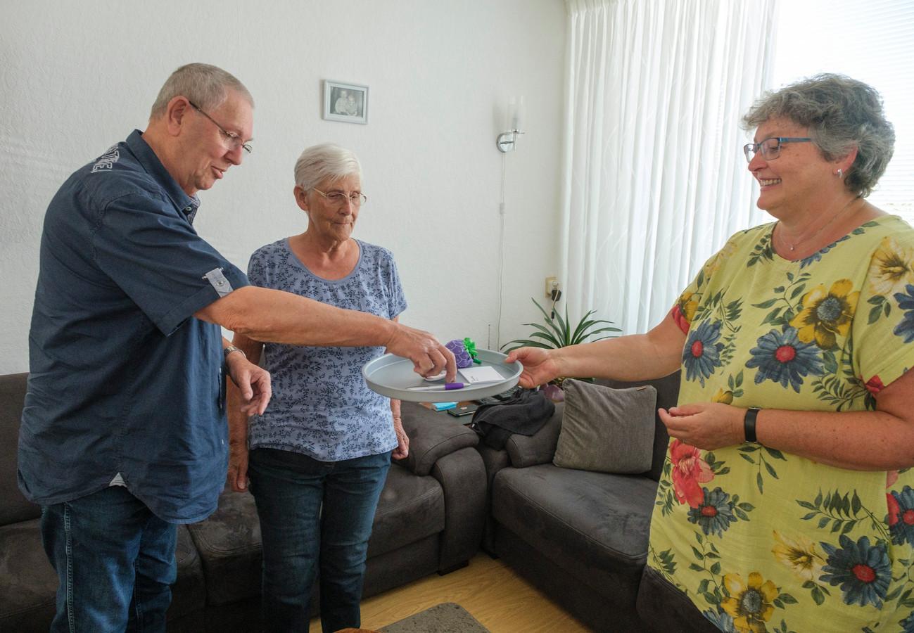 John en Willie van der Zwaan ontvangen de button van coördinator Petra de Visser van Stichting Manteling.