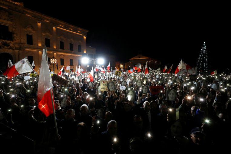 Demonstranten die de foto van de vermoordde journaliste Caruana Galizia dragen in de Maltese hoofdstad Valletta.   Beeld Reuters