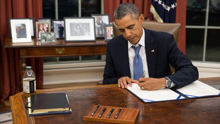 President Obama ondertekent maandagavond een regeling die voorziet in het doorbetalen van militair personeel tijdens de 'shutdown'. Beeld EPA