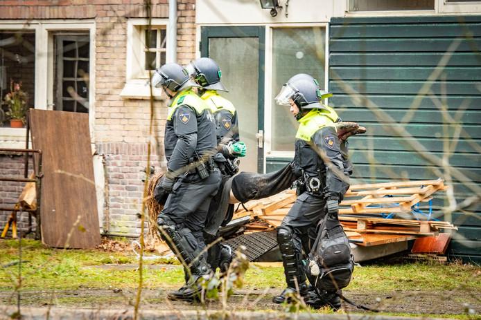 Een kraker wordt weggedragen door de politie.