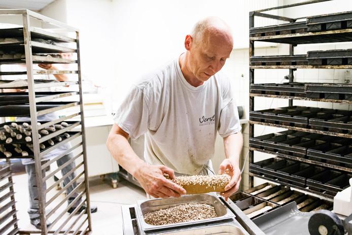 Een bakker van bakkerij Versluis is bezig met het deeg van waldkornbrood, populair vanwege de zadenmix van sesam, lijnzaad, zonnebloempitten en havermout.