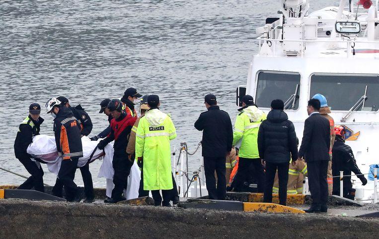 Reddingswerkers bergen de lichamen van de opvarenden van de Zuid-Koreaanse vissersboot.
