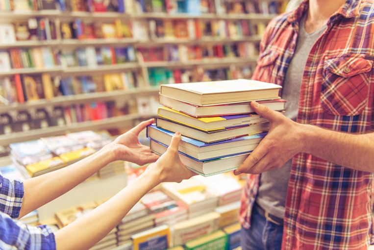 Cropped image of young man and woman holding a pile of books while standing in the book shop