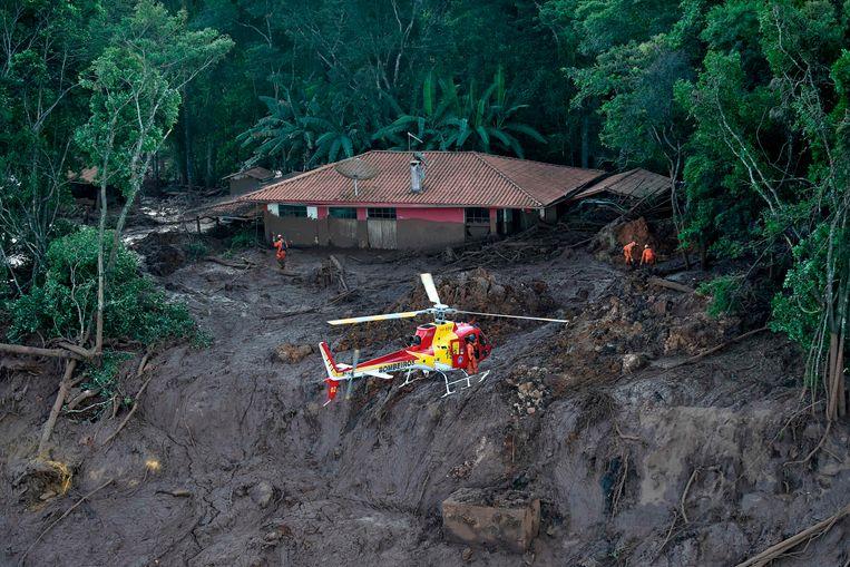 Een huis is helemaal besmeurd met modder na de dambreuk. Reddingswerkers blijven zoeken naar overlevenden.