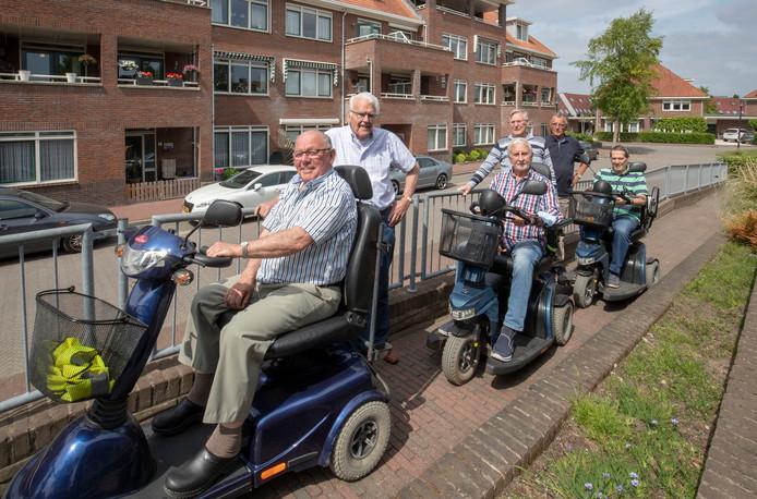 Nees van Kruistum (voorste scootmobiel) leidt de race voor Ton Harlaar en Henk Bosman. Bij het hek (van links naar rechts) Rinus Zandee, Ger van de Krogt en Herman Kuipers.