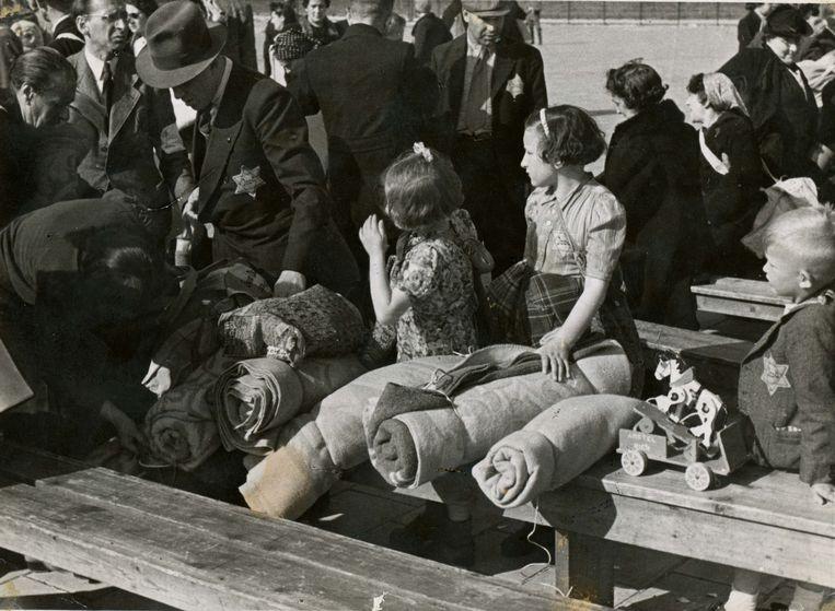 Amsterdam, 25 mei 1943. Joden moeten zich op bevel van de Zentralstelle für jüdische Auswanderung melden aan de Polderweg voor vertrek naar Westerbork. Treinen van de NS staan op het perron en brengen hen naar het kamp. NSB-fotograaf Bart de Kok maakte een reportage in opdracht van de SS. Beeld Bart de Kok/Niod, Beeldbank WO2
