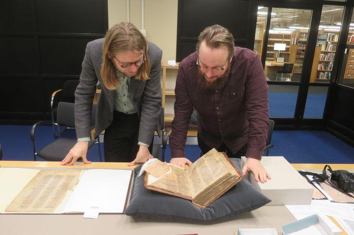 Onderzoekers Stef Uijens (l) en Daan Doesborgh bestuderen het fragment in de Koninklijke Bibliotheek.