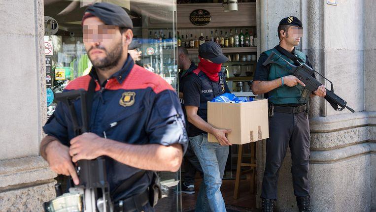 Een Spaanse agent neemt goederen in beslag tijdens een van de invallen.