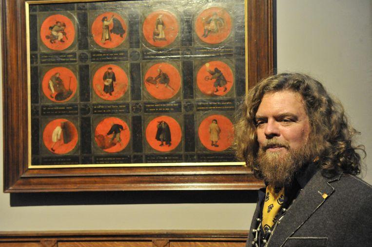 Jeroen Olyslaegers bij een schilderij van Pieter Bruegel, bestaande uit 12 beschilderde ronde medaillons.