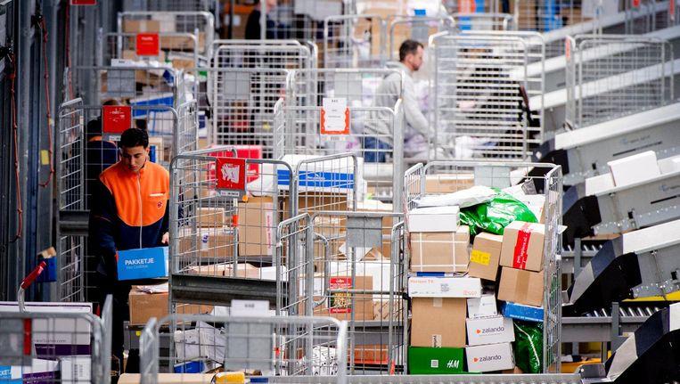 Medewerkers sorteren pakketten. Beeld ANP