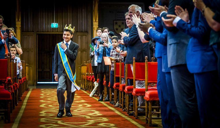 Koning van de Jeugd, Yusuf Khalid, tijdens Kleine Prinsjesdag in de Ridderzaal. De 14-jarige Koning van de Jeugd, Yusuf Khalid, draagt zijn troonrede voor in de Haagse Ridderzaal en scholierenteams gaan met een aantal Tweede Kamerleden in debat. Beeld ANP