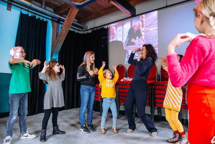 Frieda de Rhoter tussen de enthousiaste kinderen tijdens de opening. Samen met haar man Jaap heeft ze het na een jaar voor elkaar: de theaterschuur is een feit.