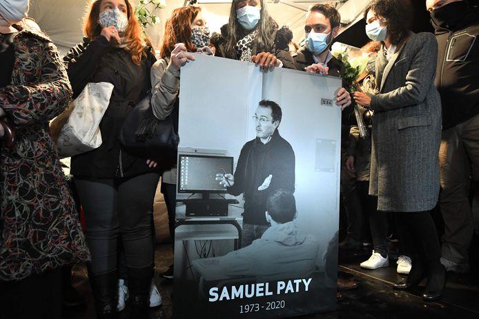 Familieleden en collega's met een foto van Samuel Paty tijdens de 'Witte Mars' ter nagedachtenis aan hem in Conflans-Sainte-Honorine ten noordwesten van Parijs.