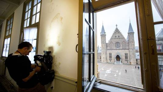 Een cameraman filmt vochtplekken in een van de gebouwen aan het Binnenhof.